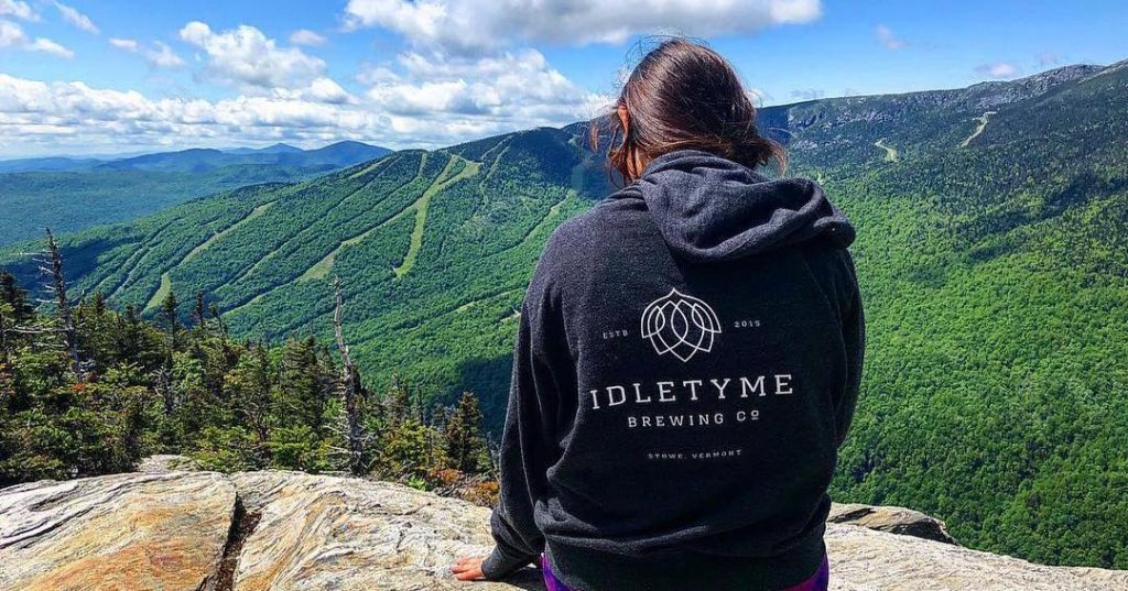 photo of a person wearing a custom sweatshirt with Idletyme Brewing Company Logo